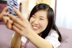 Aziatische Amerikaanse vrouw in bed die selfie het glimlachen nemen stock afbeeldingen
