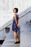 Aziatische Amerikaanse Vrouw die in Bloemenkleding over Schouder kijken Stock Afbeelding
