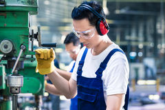 Aziatische arbeider in de boring van de productiefabriek royalty-vrije stock afbeelding