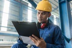 Aziatische arbeider het schrijven observaties over productie stock afbeeldingen