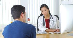 Aziatische arts het herzien röntgenstraal met patiënt Stock Afbeeldingen