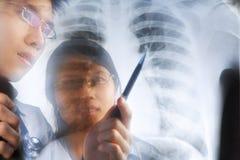 Aziatische artsen die bespreking over xray af:drukken hebben Stock Afbeeldingen