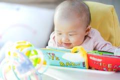 Aziatische baby gelukkig in de ruimte Aziatisch babymeisje die op bed liggen stock afbeelding