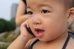 Aziatische baby in slingerkostuum, dat aan een cellphone fluistert Royalty-vrije Stock Afbeelding