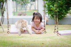 Aziatische babybaby op schommeling met puppy Stock Foto