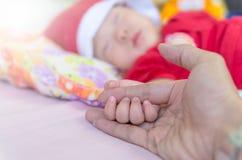 Aziatische babyhand op de volwassen hand royalty-vrije stock foto