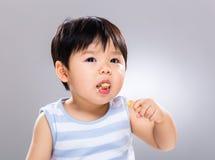Aziatische babyjongen die koekje eten stock foto