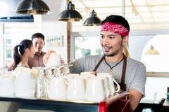Aziatische barista die espresso voor klantenpaar voorbereiden Royalty-vrije Stock Fotografie