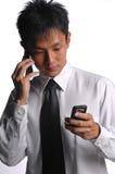 Aziatische bedrijfsmens bezig met veelvoudige handphones Royalty-vrije Stock Afbeeldingen