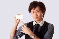 Aziatische bedrijfsmens die op witte kaart richt stock foto's