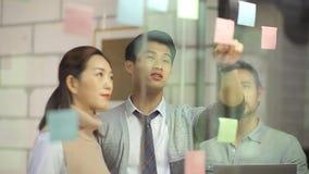 Aziatische bedrijfsmensen die in bureau samenkomen stock video