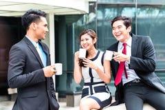 Aziatische bedrijfsmensen die koffie buiten drinken Stock Afbeeldingen