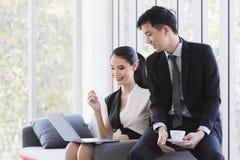 Aziatische bedrijfsmensen die laptop in bureau met behulp van stock foto's