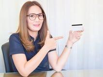 Aziatische bedrijfsvrouw die in bureau werken en toon de Creditcards Financieel van Vrouwen, concept Royalty-vrije Stock Afbeeldingen