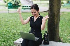 Aziatische bedrijfsvrouw die en op twee handen glimlacht opheft om voor succesvolle zaken te vieren zij zitting in de tuin met la stock afbeelding