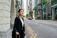 Aziatische bedrijfsvrouw die op taxicabine wachten Stock Foto's