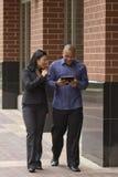Aziatische bedrijfsvrouw en man die en met tablet lopen spreken stock foto