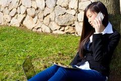 Aziatische bedrijfsvrouw in park die met de telefoon en de tablet van PC werken stock afbeelding