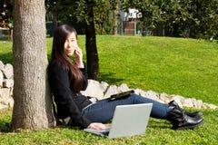 Aziatische bedrijfsvrouw in park die met PC-telefoon werken en tablet die camera kijken stock foto's