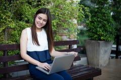 Aziatische bedrijfsvrouwen die notitieboekje voor het werken gebruiken bij openlucht Royalty-vrije Stock Fotografie
