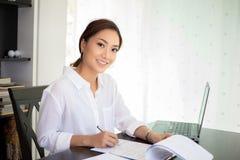 Aziatische bedrijfsvrouwen notitieboekje gebruiken en glimlachen die gelukkig voor worki stock afbeeldingen