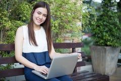 Aziatische bedrijfsvrouwen notitieboekje gebruiken en glimlachen die gelukkig voor workin royalty-vrije stock foto's