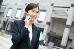 Aziatische bedrijfsvrouwenbespreking aan mobiele telefoon stock fotografie