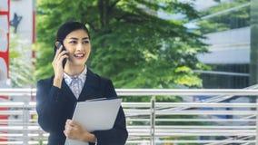 Aziatische bedrijfsvrouwengebruik en besprekingen op mobiele telefoon royalty-vrije stock afbeelding