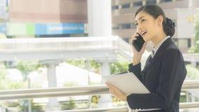 Aziatische bedrijfsvrouwengebruik en besprekingen op mobiele telefoon met document w stock fotografie