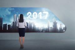 Aziatische bedrijfsvrouwenglimlach met de wolkenvorm van 2017 op de rug Royalty-vrije Stock Afbeelding