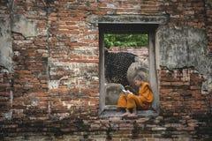 Aziatische Beginnermonniken die het heilige boek op het terras van Boeddhistische tempel lezen royalty-vrije stock foto