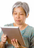 Aziatische bejaarde gebruikende tablet Stock Foto's