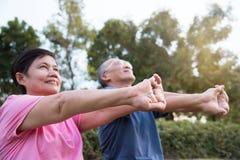 Aziatische bejaarde mensen die zich vóór oefening uitrekken stock afbeelding