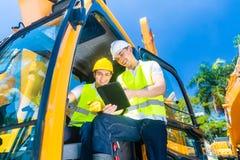 Aziatische bouwbestuurder die met ingenieursblauwdrukken bespreken Stock Foto's
