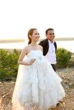 Aziatische bruid en bruidegom in huwelijkskleding tegen de zonsondergangscène Stock Foto
