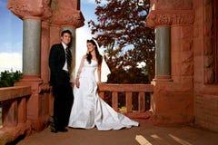 Aziatische Bruidegom die terwijl Zijn Bruid hem bekijkt glimlacht stock foto's