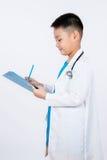 Aziatische Chinese jongen die als arts met klembord beweren Royalty-vrije Stock Afbeeldingen