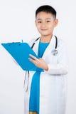 Aziatische Chinese jongen die als arts met klembord beweren Stock Afbeelding