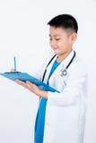 Aziatische Chinese jongen die als arts met klembord beweren Stock Afbeeldingen
