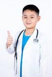Aziatische Chinese jongen die als arts met omhoog duimen beweren Stock Fotografie