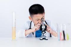 Aziatische Chinese jongen die met microscoop werken Royalty-vrije Stock Foto