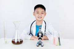 Aziatische Chinese jongen die met microscoop werken Stock Foto