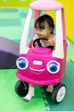 Aziatische Chinese meisje drijfstuk speelgoed auto stock afbeelding