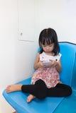 Aziatische Chinese meisjezitting binnen MRT met telefoon royalty-vrije stock fotografie