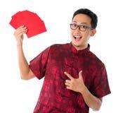 Aziatische Chinese mens die vele rode pakketten tonen Stock Foto's