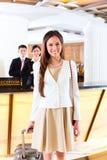 Aziatische Chinese vrouw die bij hotel voorbureau aankomen Royalty-vrije Stock Afbeelding