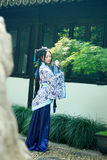 Aziatische Chinese vrouw in traditionele Blauwe en witte Hanfu-kleding, spel in een beroemde tuin dichtbij vensters stock foto