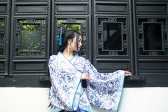 Aziatische Chinese vrouw in traditionele Blauwe en witte Hanfu-kleding, spel in een beroemde tuin dichtbij vensters royalty-vrije stock foto