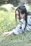 Aziatische Chinese vrouw in traditionele Blauwe en witte Hanfu-kleding, spel in een beroemde tuin, die zich onder bloemen bevinde stock foto's