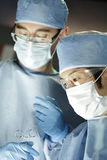Aziatische chirurg die met medewerker in chirurgie werken stock afbeeldingen